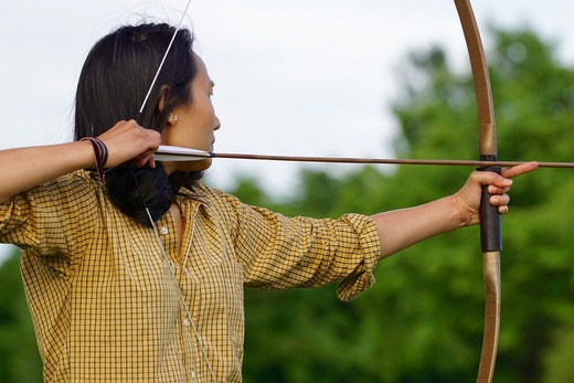 An Asian man using a bow and arrow