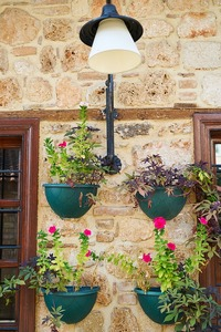 Four potted flowers on a wall, under a light outside