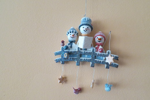 Small Christmas figurines hanging on a wall