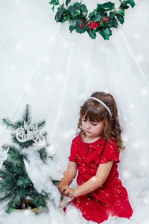 A girl in a red dress arranging a small Christmas tree