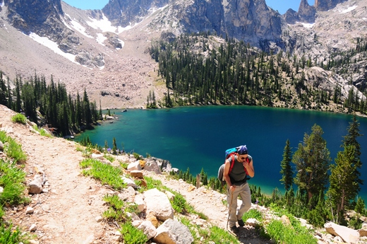 Man hiking in the mountains by a small blue lake