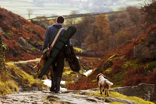 A man going hunting with his dog.