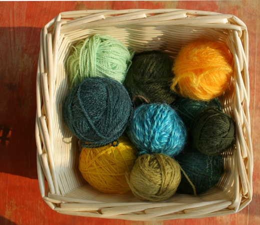 Wicker basket with balls of coloured knitting yarn