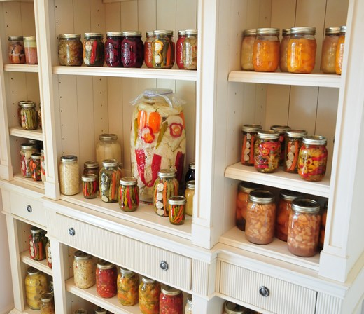 Pickled vegetable jars neatly stacked in an old cabinet.